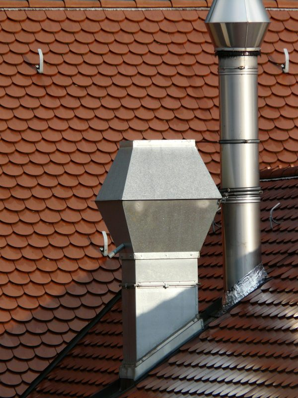 This Philadelphia building has two stainless steel chimney liners and chimney caps coming out of a slanted roof made from flat red tiles.