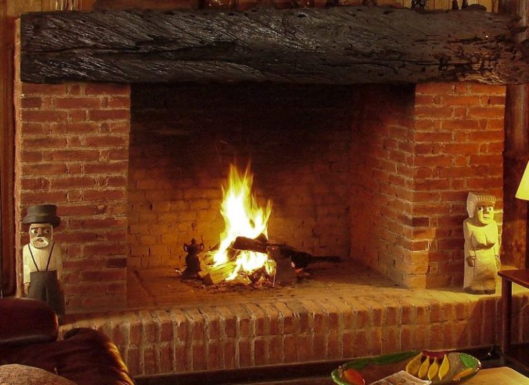 Shown is a red brick chimney in Philadelphia with a large hearth that needs sweeping. To either side are two wood statues. Above is a large wood mantel.