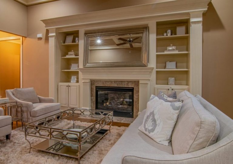 Pictured in the background is a gas fireplace within an ornate design feature in Philadelphia. In the foreground is a modern white couch