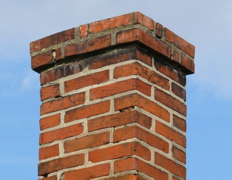 This red brick chimney in Philadelphia has recently had a chimney inspection rated in good condition. The background is a blue sky.
