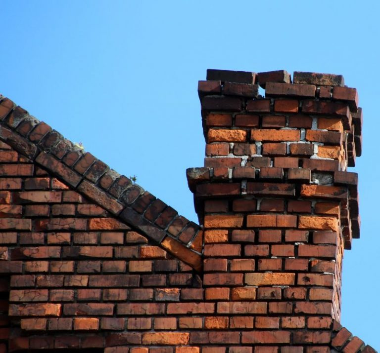 Here is an old brick chimney under inspection in Philadelphia. The mortar on the top of the chimney is missing so the bricks are simply stacked on top. In the background is blue sky.