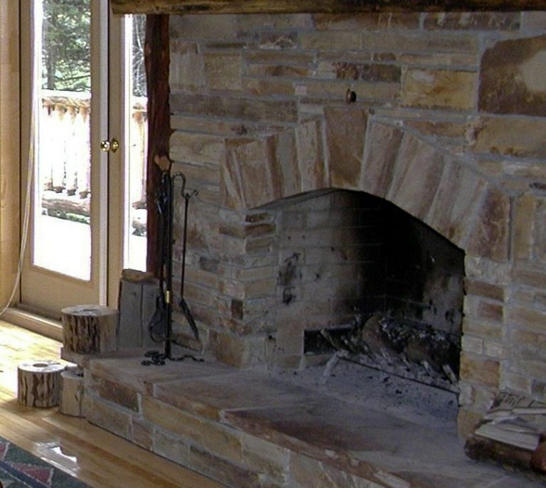 Here is a dirty stone fireplace in Philadelphia that needs fireplace cleaning. There's white ash everywhere and burn marks on the back of the firebox.