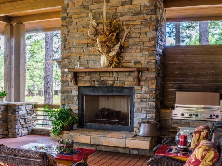 You are looking at a stone fireplace undergone chimney repair and maintenance surrounded by large glass windows looking out into trees outside of Philadelphia